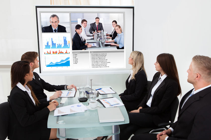 28753871 - businesspeople looking at projector screen in video conference meeting at office