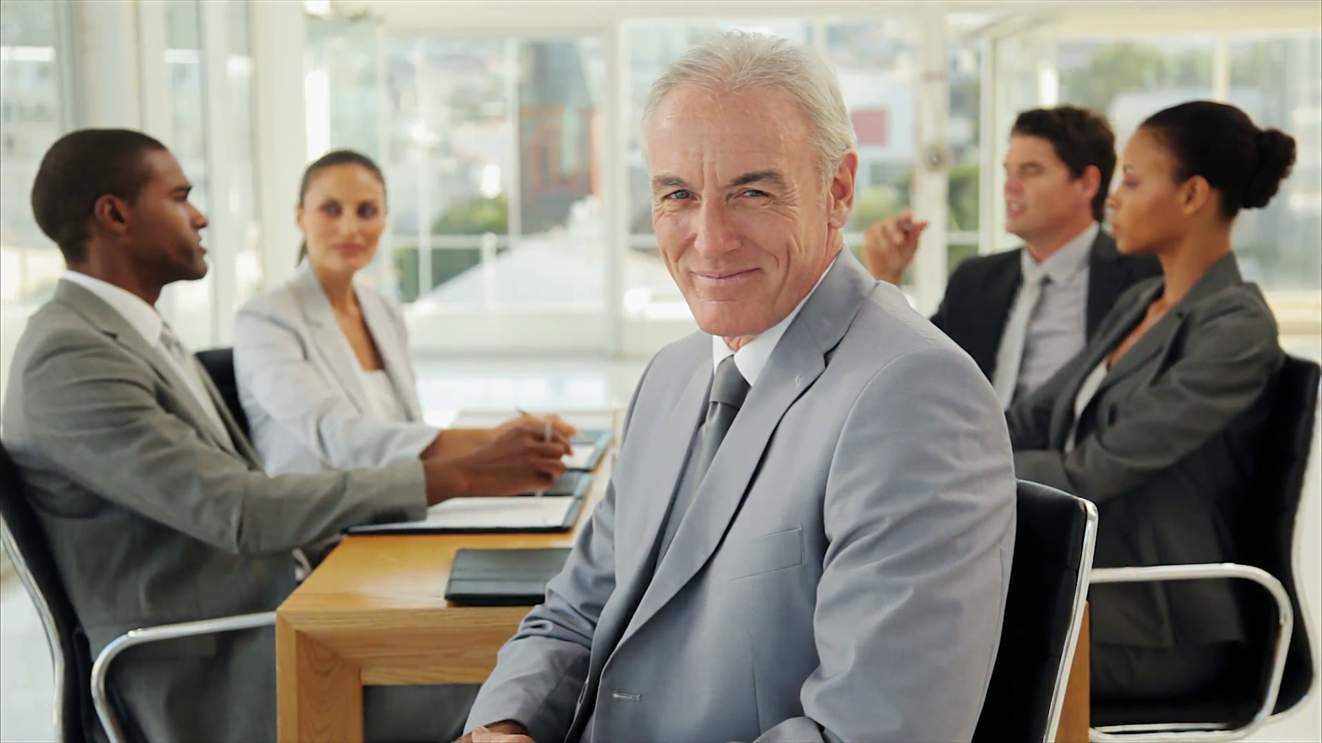 businessman-sitting-at-the-head-of-boardroom-table-in-a-business-meeting-his-business-colleagues-are-having-a-discussion-in-the-background_vmmhjt53g__F0010